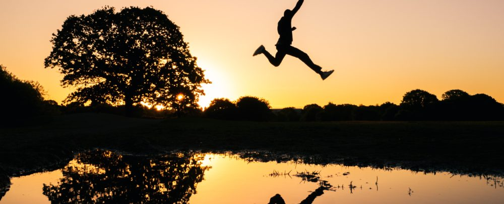 A guy is jumping into a river at sunset