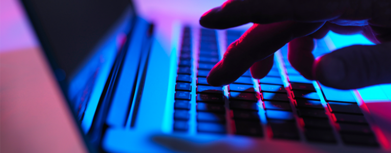 Fingers Typing on Laptop Protected by Email Security Solution