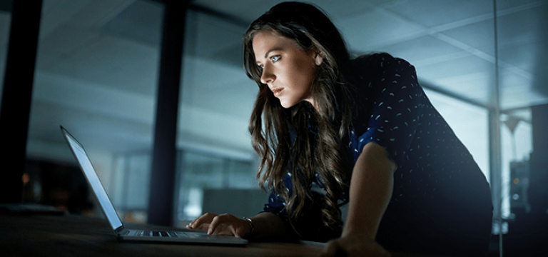 Woman Uses Laptop Protected by Digital Security Risk Solution