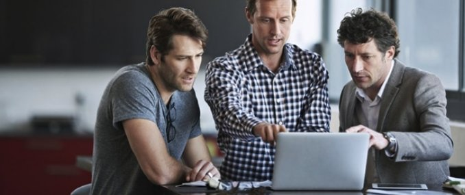 Male Employees Standing In Front of Laptop Protected by Cloud App Security